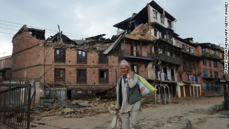 A man walks next to collapsed houses in Bhaktapur, on the outskirts of Kathmandu, on April 27, 2015, two days after a 7.8 magnitude earthquake hit Nepal.