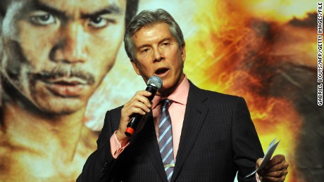 Michael Buffer speaks in front of a poster of Manny Pacquiao.