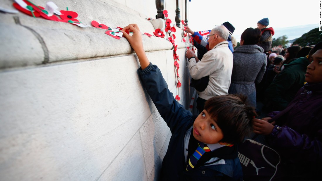 APRIL 25 - AUCKLAND, NEW ZEALAND: People pin poppies to the Cenotaph following the Dawn Service at the Auckland War Memorial Museum on ANZAC Day, the 100th anniversary of the 1915 Gallipoli landings.