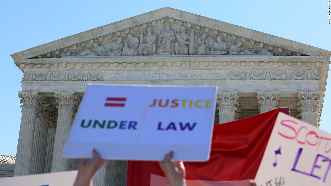 "Outside the Supreme Court of the United States, people hold signs calling for ""equal justice under law."""
