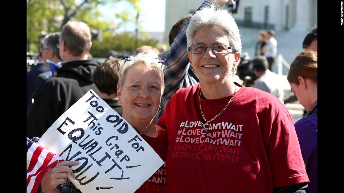 Stephanie Jones and Diana Iwanski of Clermont, Florida, share their sign in support of same-sex marriage outside the Supreme Court.