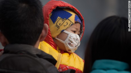 An infant wearing a mask was carried along a street in severe pollution in Beijing on January 12, 2013, a hazardous day when the PM 2.5 data released via the US embassy twitter was 519 on a scale that stops at 500.