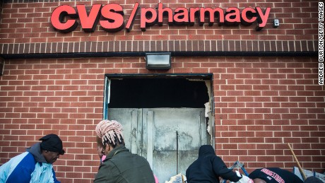 Members of the community on April 28 clean up debris from the CVS that was burned and looted in the riots.
