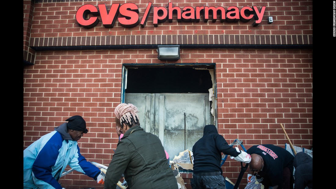 Members of the community clean up debris on April 28 from the CVS that was burned and looted in the riots.