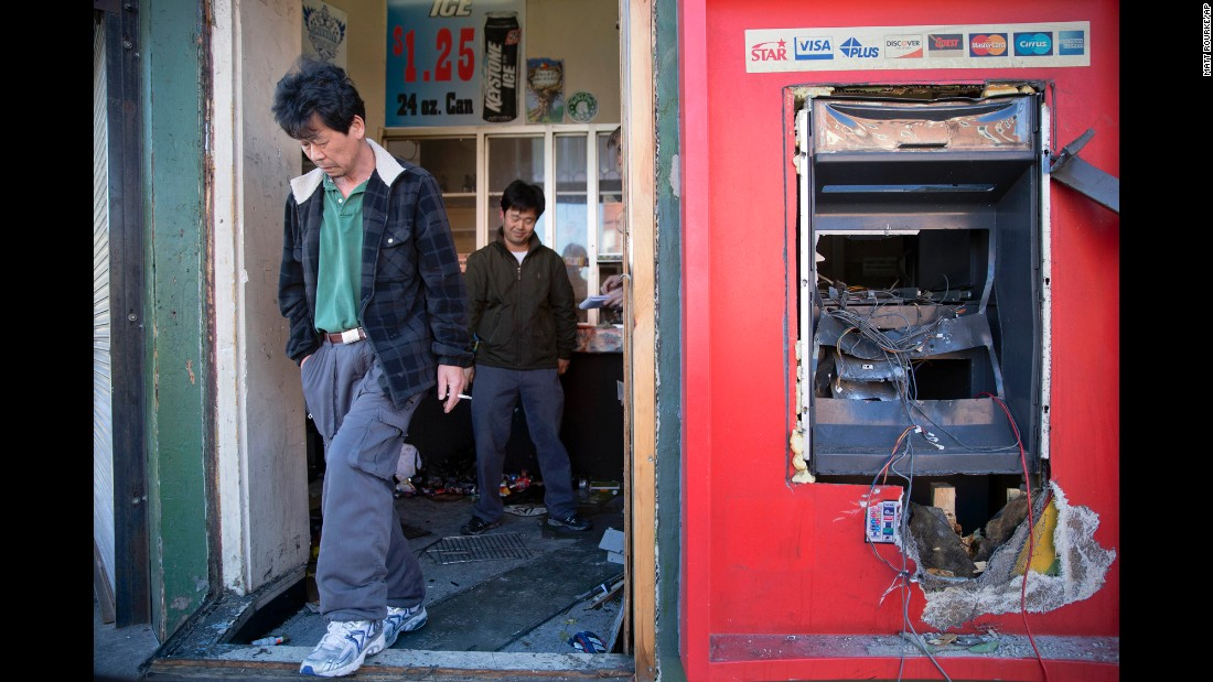 Jason Park, left, and business owner Sung Kang survey the damage to his store on April 28.
