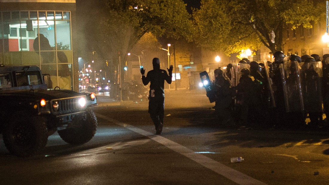 "A community organizer later identified as Joseph Kent paces in front of riot police with his hands up during a curfew in Baltimore on Tuesday, April 28. Moments later, he was seen being <a href=""http://www.cnn.com/videos/us/2015/04/29/ctn-live-cuomo-baltimore-joseph-kent-arrested.cnn"">arrested by police live on CNN</a>. Kent's lawyer said on April 30 that his client had been released from jail. While some protesters defied the curfew and faced off with police, demonstrations Tuesday were largely peaceful."