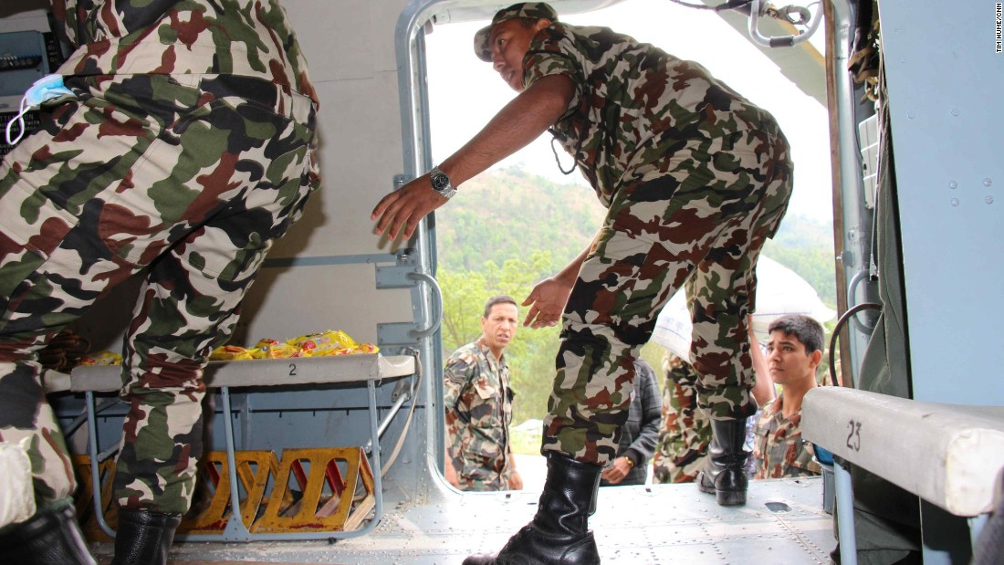 Nepalese soldiers offload much needed aid supplies, including packages of rice, noodles and tuna, medicine and tents once they land in Melamchi.