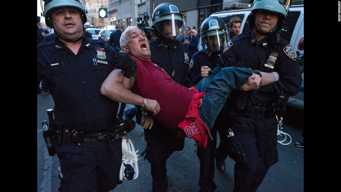 Police officers carry a man away in Union Square in New York on April 29. More than 100 people were arrested during demonstrations, New York police said.