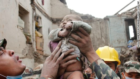 "In this Sunday, April 26, 2015, photo taken by Amul Thapa and provided by KathmanduToday.com, four-month-old baby boy Sonit Awal is held up by Nepalese Army soldiers after being rescued from the rubble of his house in Bhaktapur, Nepal, after Saturday's 7.8-magnitude earthquake shook the densely populated Kathmandu valley.  Thapa says that when he saw the baby alive after 20 hours of rescue efforts ""... all my sorrow went. Everyone was clapping. It gave me energy and made me smile in spite of lots of pain hidden inside me."" (Amul Thapa/KathmanduToday.com via AP)"