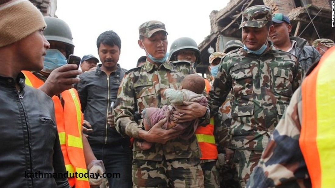 A soldier cradles the baby after he was pulled from the debris.