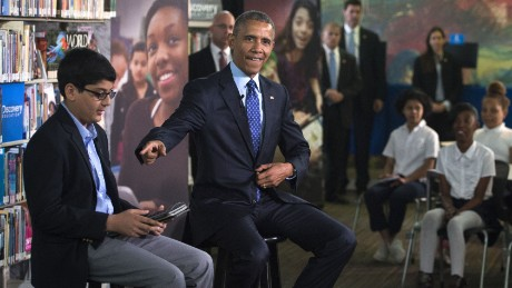 U.S. President Barack Obama (R), with student moderator Osman Yaya (L), responds to a question during a 'Virtual Field Trip' with middle school students from around the country at Anacostia Library April 30, 2015 in Washington, DC. Students countrywide participated to discuss efforts to increase learning opportunities with improving access to digital reading content and public libraries.