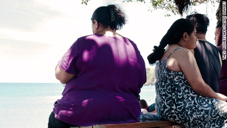 People sit along the beach in Noumea on December 1, 2014. Obesity and diabetes are affecting citizens throughout the South Pacific islands, proportionately among the highest in the world, due to the change in eating habits and lifestyles as well as a genetic predisposition.
