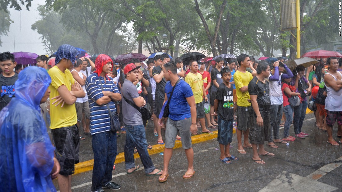 Fans brave a heavy downpour as they watch a live telecast of fight in Marikina, Philippines.