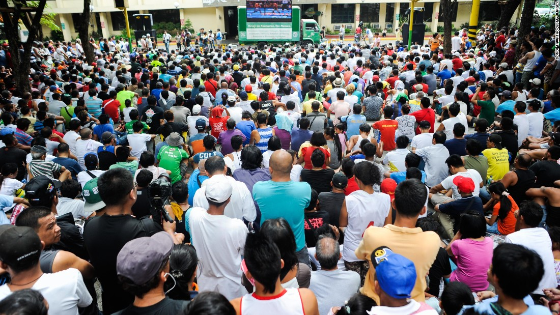 Filipinos consider Pacquiao a national hero. He is an elected member of the national Congress, the coach and player on his own professional basketball team, and a real-life rags-to-riches success story. Here people watch the bout at a public plaza in Marikina City, Philippines.