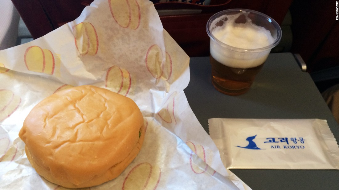 The inflight meal consists of a burger and a glass of North Korean beer.