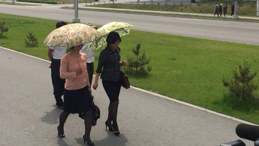 Pyongyang women wear their Sunday best -- and carry ornate umbrellas to shield themselves from the sun.