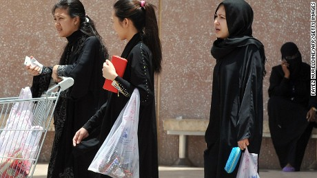 Domestic workers  carry shopping bags as they walk out of a mall in Riyadh, on June 12, 2013.