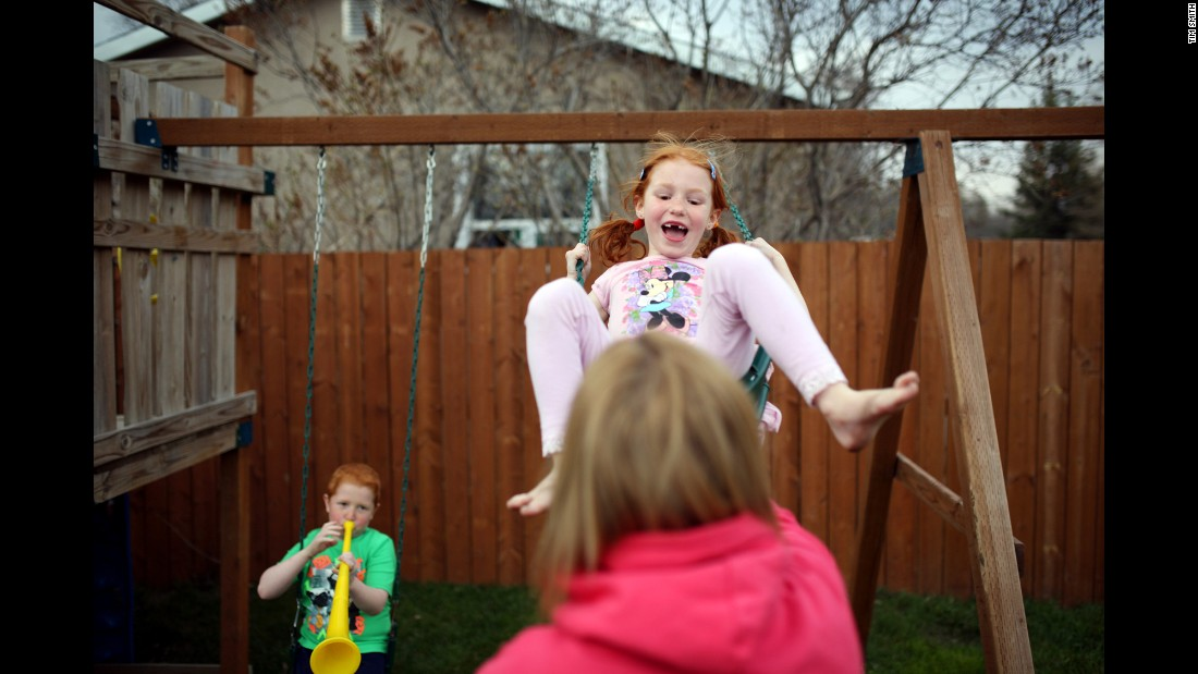 Emily laughs as Cheryl plays with her in the backyard of their home in Manitoba. She is her brother and mother's biggest cheerleader. For weeks after Cheryl's diagnosis, she would make her mother cards as soon as she walked in the door from school.