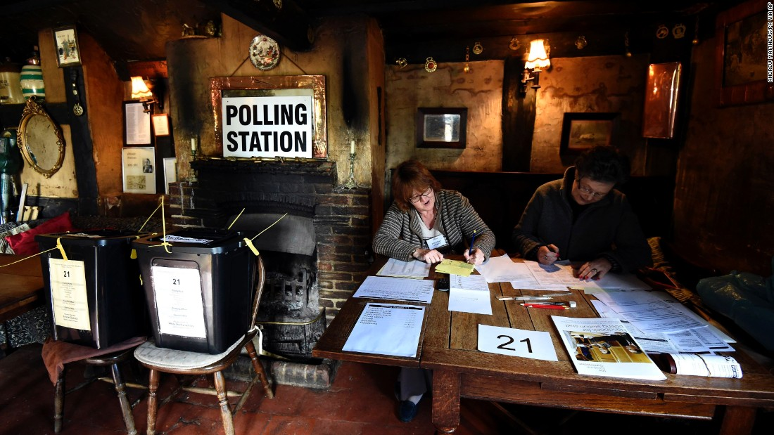 Election officials work at a polling station in the White Horse Inn in Priors Dean, England.
