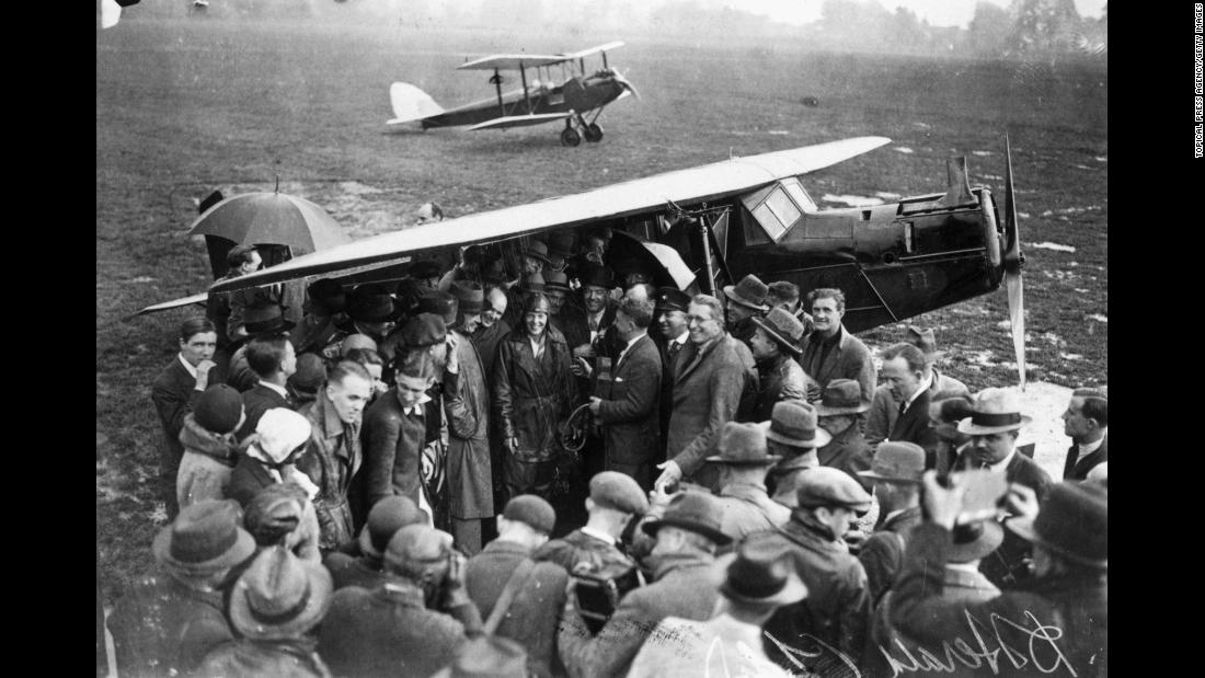 Earhart is surrounded by a crowd of well-wishers and journalists in London following her historic flight. She is being congratulated here by Andrew Mellon, the United States ambassador to Britain.