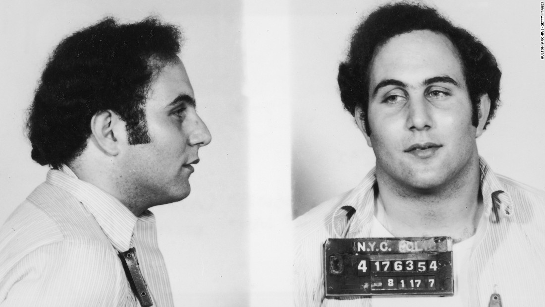 "A police mug shot showing New York City serial killer David Berkowitz, known as the ""Son of Sam"" and the ""44 Caliber Killer.""  Berkowitz killed six people and wounded seven others between 1976 and 1977, mostly young women and couples in secluded locations. At the time of his arrest, he claimed a demon spoke to him through a neighbor's dog. He is currently serving consecutive life sentences totaling more than 300 years."