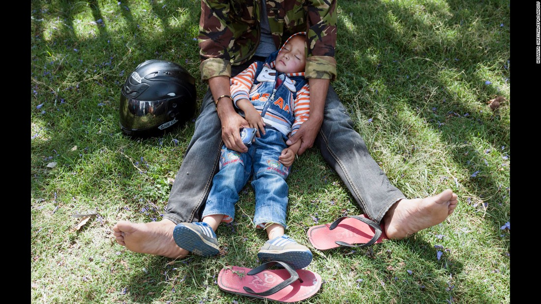 A boy sleeps in his father's lap after they moved to an open area in the Tundikhel area of Kathmandu on May 12.