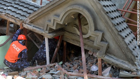 Rescue team officials and a sniffer dog search for survivors at a collapsed house in Kathmandu May 12, 2015, after an earthquake struck. A 7.4-magnitude earthquake hit has devastated Nepal, sending terrified residents running into the streets in the capital Kathmandu, according to witnesses and the US Geological Survey.