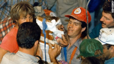 A rescue worker carries18-month-old Jessica McClure to safety in Midland, Texas after she was trapped for 58 hours after she plunged 22 feet into an abandoned water well.