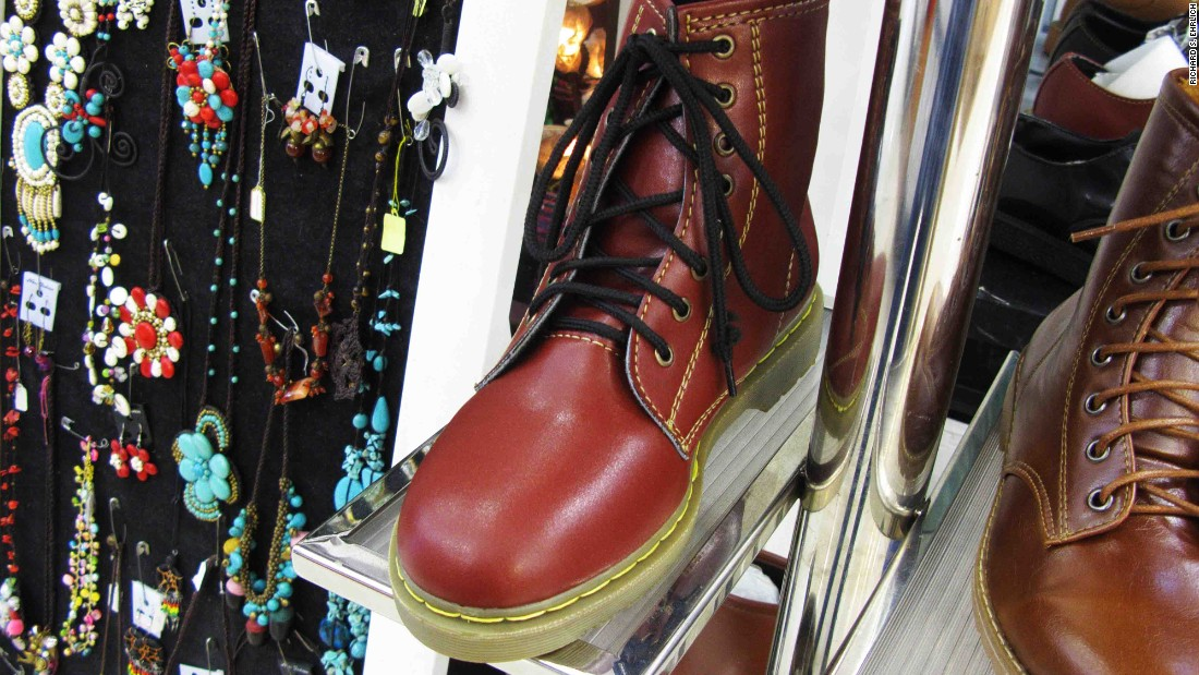 "In an air-conditioned, multi-level mall in Bangkok, a sign deceptively advertises ""Dr. Martens"" next to boots resembling the real thing, but without any logos on the leather or soles."