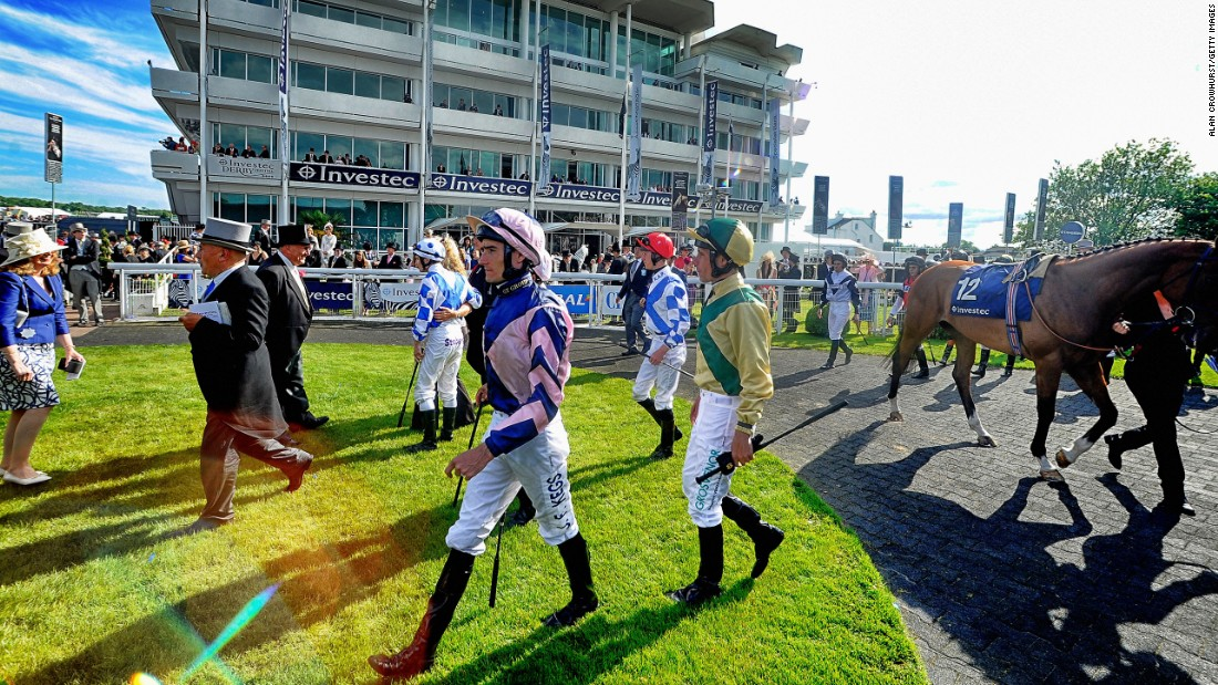Ahead of each race, jockeys make their way into the parade ring to meet the owners and saddle up on their mounts.