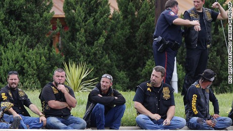 Bikers wait in a line as law enforcement officers investigate the shooting.