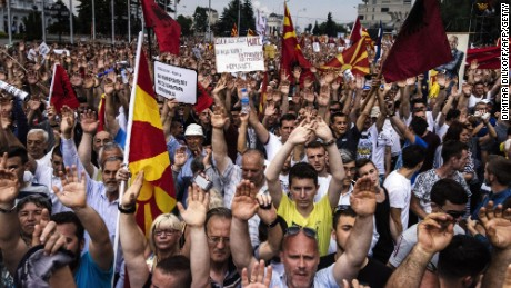 People wave Macedonian flags and raise their hands during an anti-government protest in downtown Skopje on May 17.