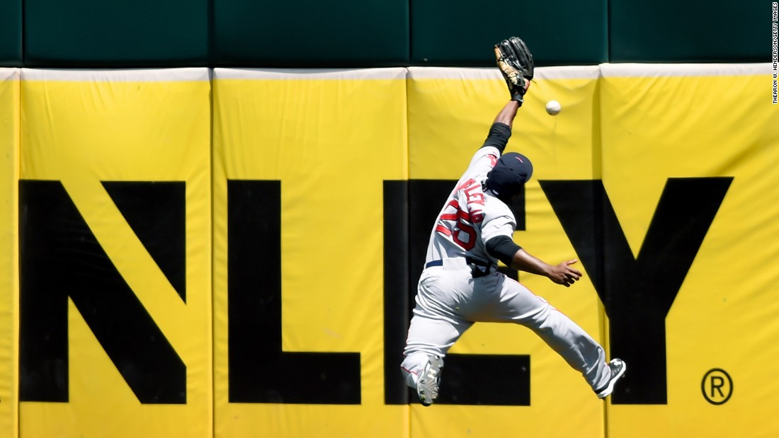 Boston's Jackie Bradley Jr. leaps near the outfield wall but can't make the catch during a game in Oakland, California, on Wednesday, May 13.