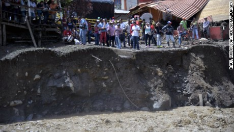 People remain at the area of a landslide in Salgar municipality, Antioquia department, Colombia on Monday, May 18, 2015. A massive landslide tore through a ravine in northwest Colombia Monday before dawn, killing 48 people and injuring 37, authorities said.