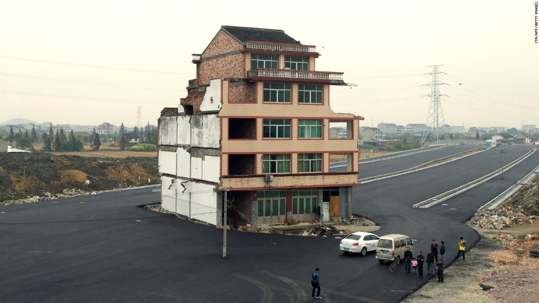 A half-demolished apartment building stands isolated in the middle of a newly-built road on November 22, 2012. Luo Baogen, 67, a duck farmer, and his 65-year-old wife refused to move out from their home in eastern China's Zhejiang province, waging a four-year long battle with the local government over a compensation plan.