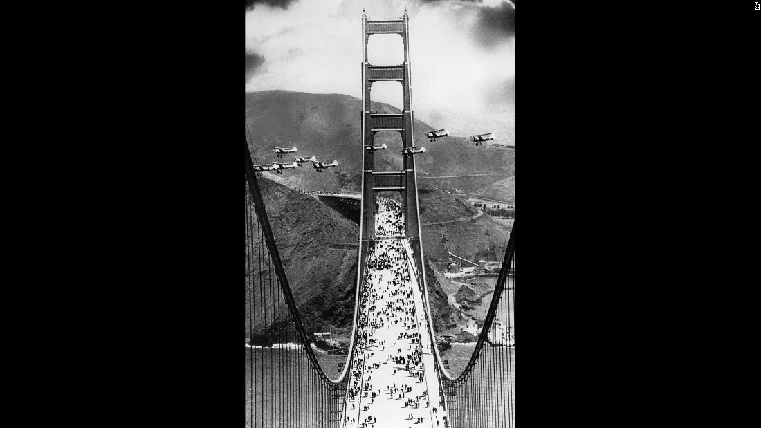 Military biplanes fly between the towers of the bridge as pedestrians walk across the 4,200-foot span during opening ceremonies on May 27, 1937.