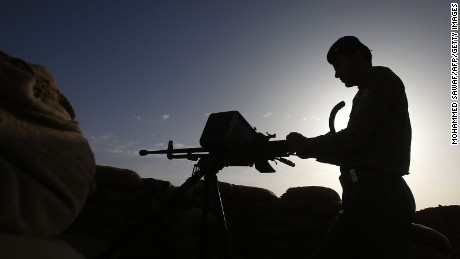 An Iraqi fighter from the Shiite Muslim Al-Abbas popular mobilization unit monitors from his position in the area surrounding the village of Nukhayb in the embattled Anbar province west of the capital Baghdad, on May 19, 2015.