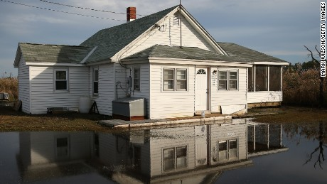 The front yard of a vacant home in Maryland is shown in 2014 flooded from rising waters.
