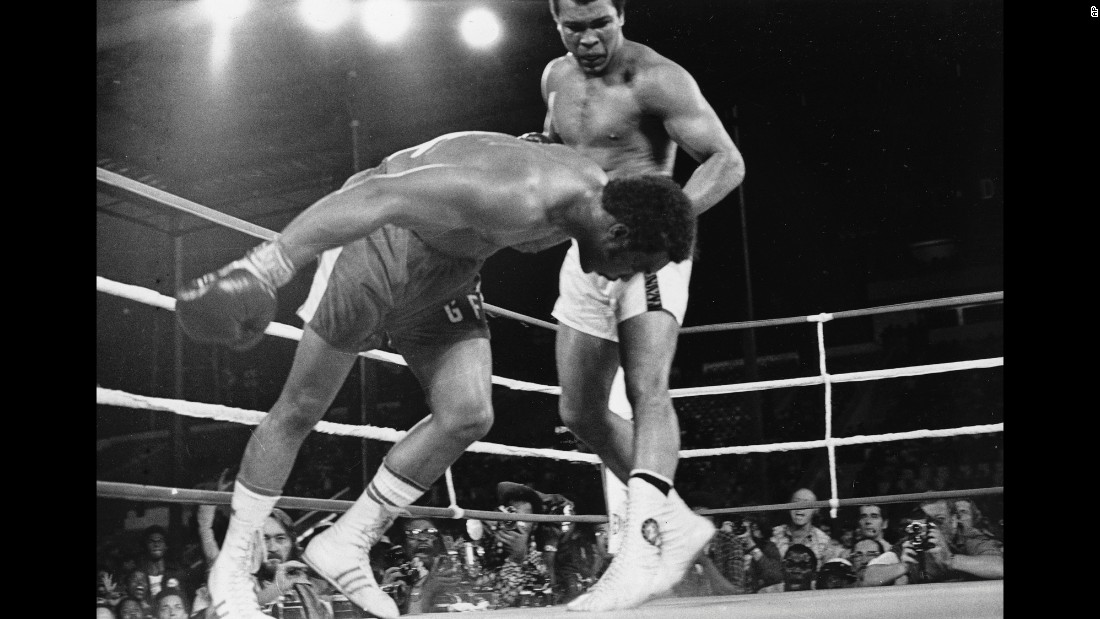 Muhammad Ali watches heavyweight champion George Foreman fall to the canvas during their title bout in Kinshasa, Zaire, in October 1974. Ali's upset victory over the undefeated Foreman won him back the titles he was stripped of in 1967 for refusing induction into the U.S. Army.