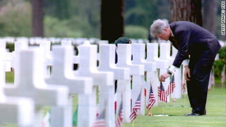 Then-President Bill Clinton adjusts a U.S. flag at the grave of Army Lt. Robert Waugh as he visits the Sicily-Rome American cemetery in June, 1994.