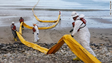 Workers prepare an oil containment boom at Refugio State Beach, north of Goleta, California, on May 21.