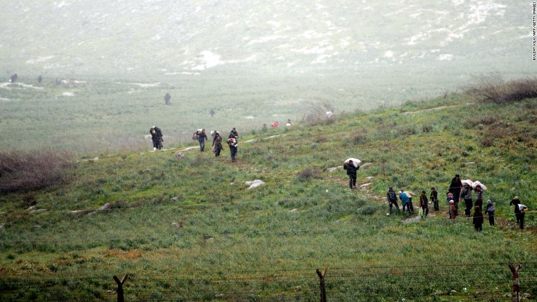 Syrian refugees walk across a field in Syria before crossing into Turkey on March 14, 2012.