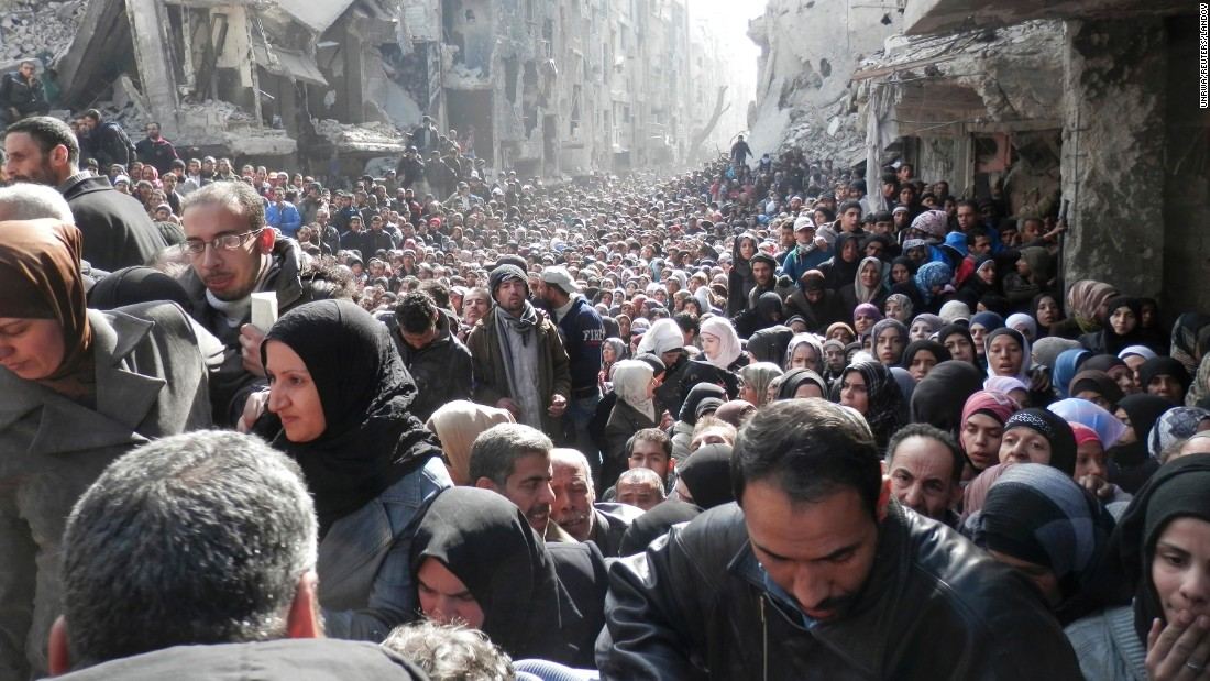 Residents wait to receive food aid distributed by the U.N. Relief and Works Agency at the besieged al-Yarmouk camp, south of Damascus, on January 31, 2014.