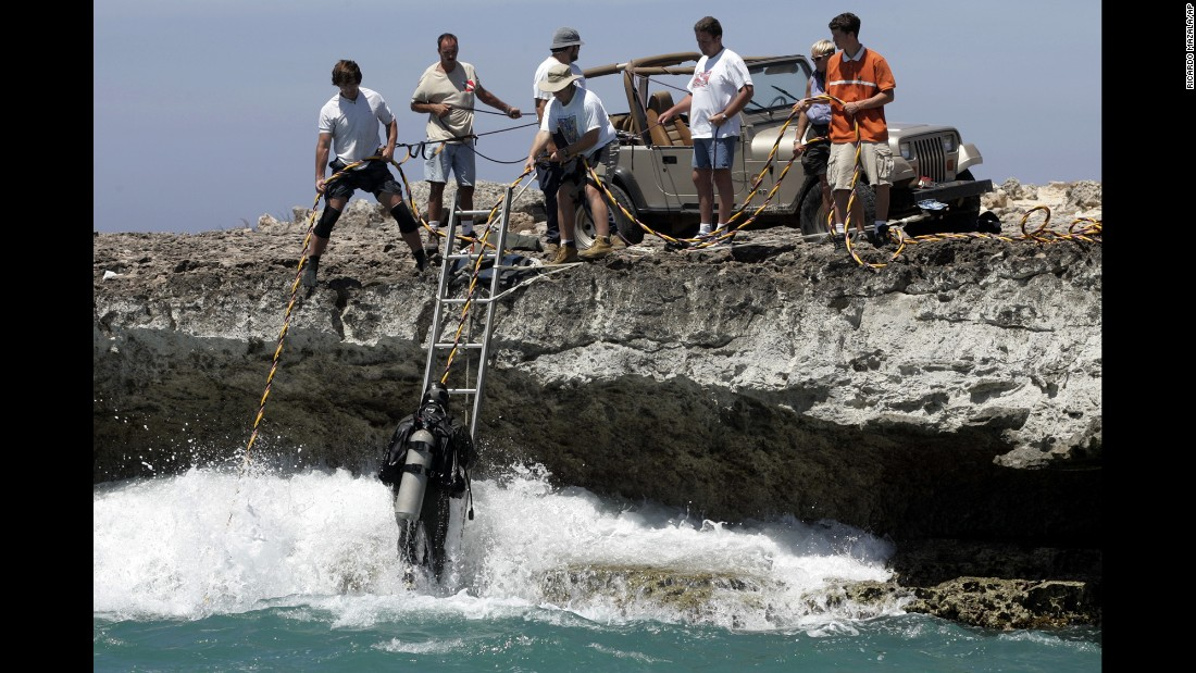 A diver from Florida State University and volunteers with Texas EquuSearch search the waters near the California Lighthouse in Aruba in July 2005.