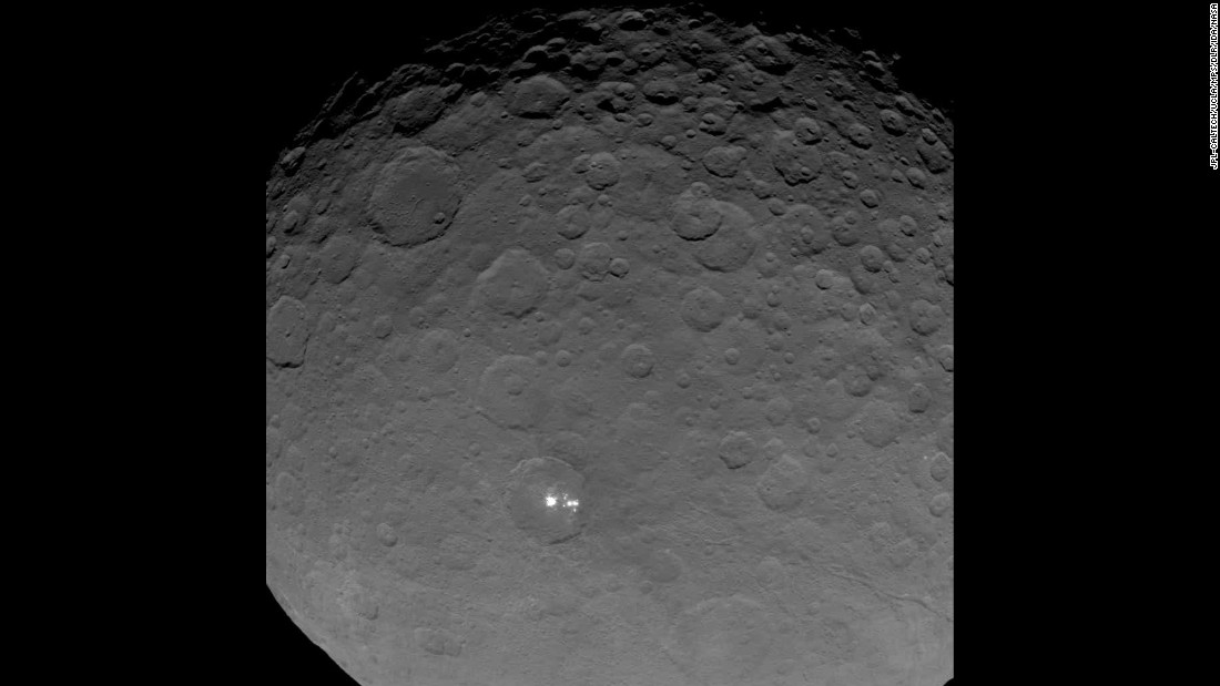 "Dawn gave scientists a big surprise: Ceres has a group of bright spots glowing inside a large crater. The above image is part of a sequence taken by Dawn on May 16, 2015 when the spacecraft was 4,500 miles (7,200 kilometers) away from Ceres. It's the closest view yet of the spots. But what are they? According to the mission's principal investigator, Christopher Russell, scientists have concluded the spots are ""due to the reflection of sunlight by highly reflective material on the surface, possibly ice."""