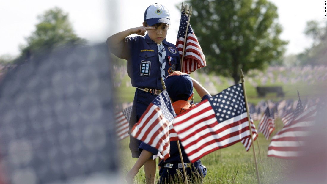 Cub Scout Tristan Swanhart salutes after he placed a flag on a grave at a veterans cemetery in Wrightstown, New Jersey, on Friday, May 22.