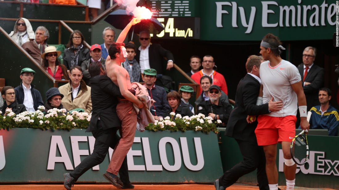 Rafael Nadal looks on as security guards restrain the protester. The Spaniard went on to beat David Ferrer in that 2013 final.