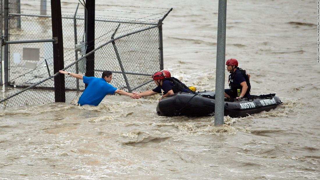 Rescue personnel grab the the hand of a man who was stranded in rushing water in Austin on May 25.
