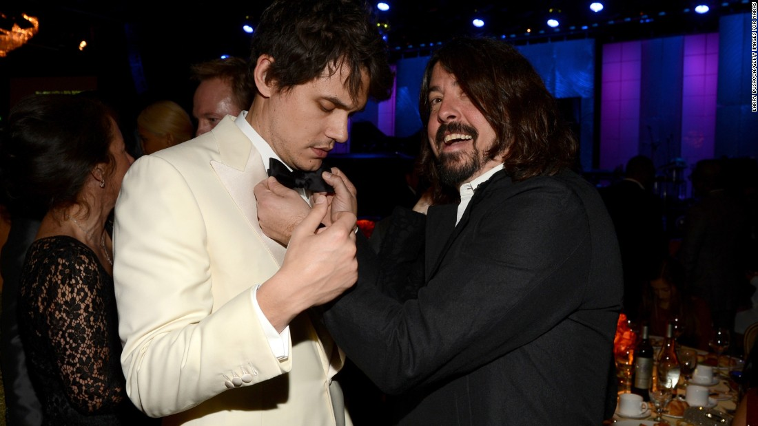 Grohl adjusts John Mayer's bow tie at the 2013 Grammy Awards.