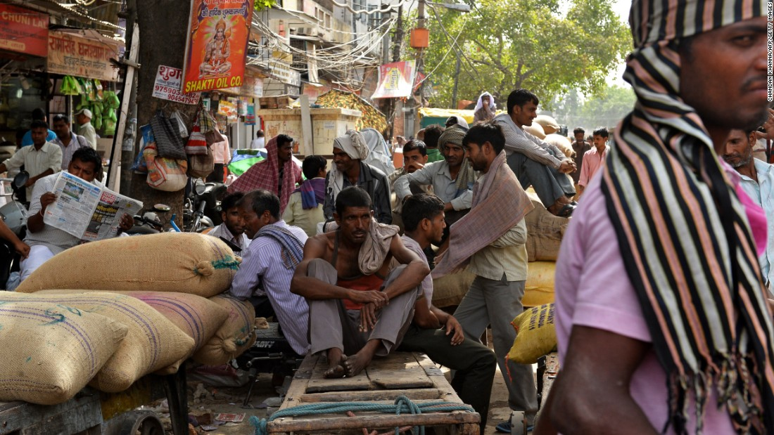 People sit in the shade of a market in New Delhi on May 26.
